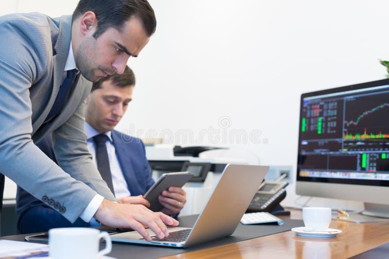 遥远地解决问题的企业队在业务会议上使用便携式计算机和触感衰减器 库存照片