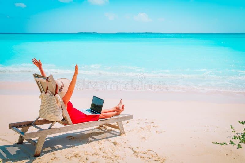 遥远的工作概念-有膝上型计算机的愉快的少妇在海滩 免版税库存照片