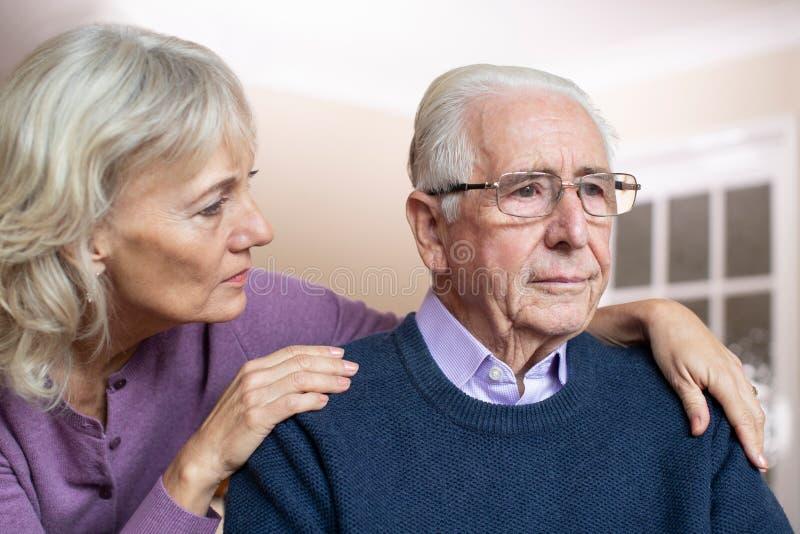 遭受与消沉和老年痴呆的被迷惑的老人被安慰由妻子 免版税库存照片