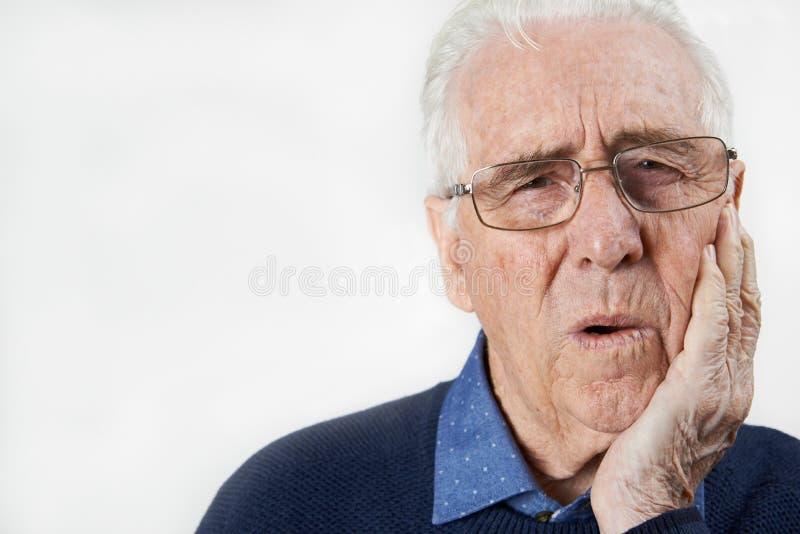 遭受与牙痛的老人演播室画象 免版税库存照片