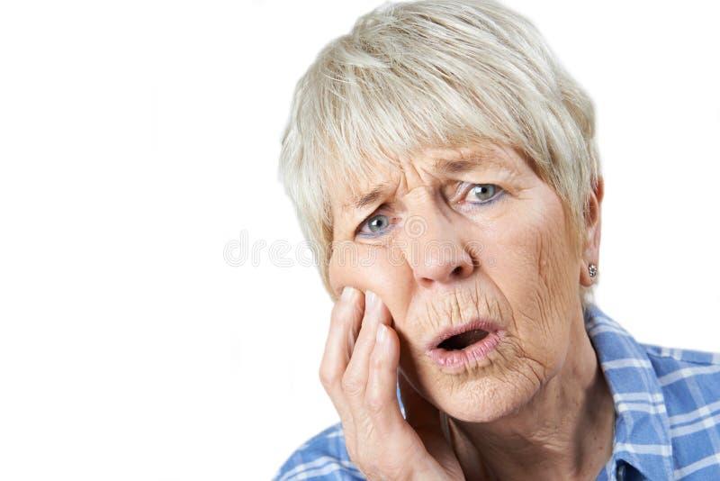 遭受与牙痛的资深妇女演播室画象 免版税库存图片