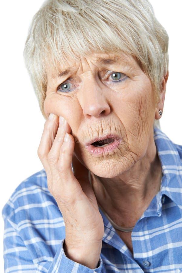 遭受与牙痛的资深妇女演播室画象 库存照片