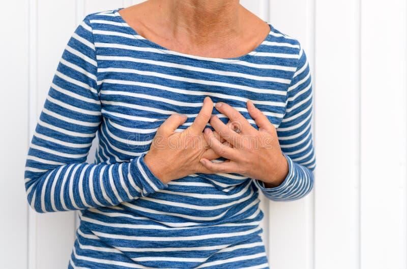 遭受严厉胸口痛的妇女 免版税库存图片