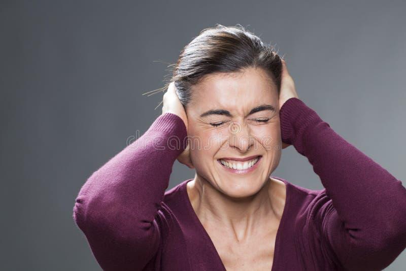 遭受偏头痛的美丽的20世纪30年代女孩包括她的耳朵用她的手 库存照片