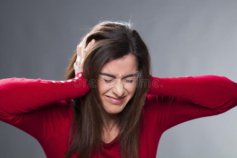 遭受偏头痛的紧张的20世纪30年代浅黑肤色的男人,包括她的耳朵用她的手 免版税库存照片