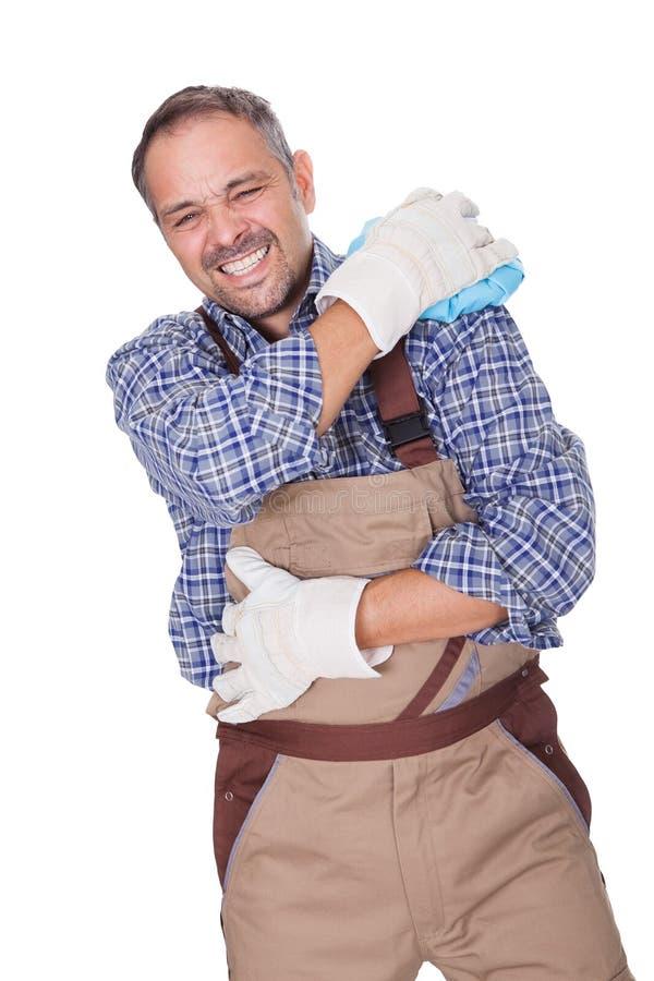 遭受充满肩膀痛苦的建筑工人 免版税库存图片