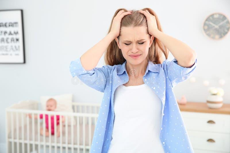 遭受出生后的消沉和小婴孩的年轻母亲 免版税库存照片