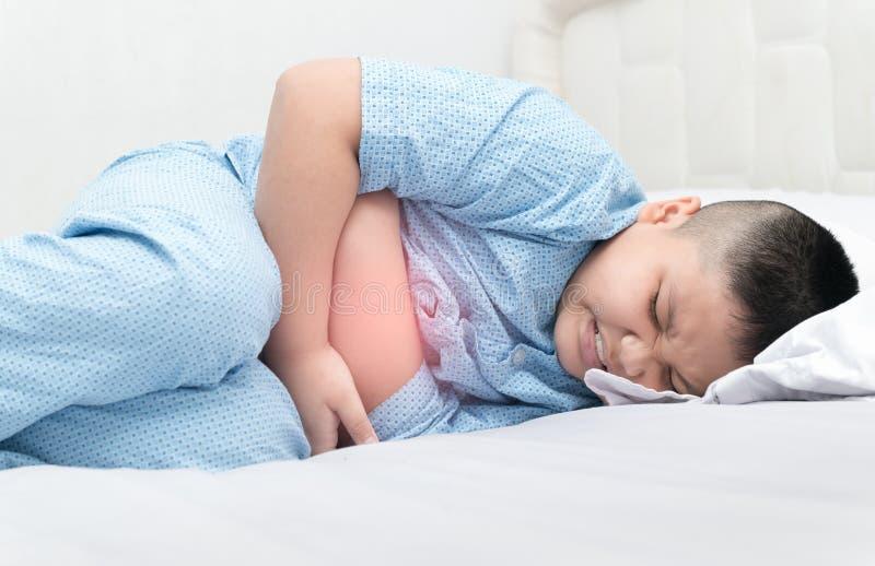 遭受在床上的stomachache的肥胖肥胖男孩 库存照片