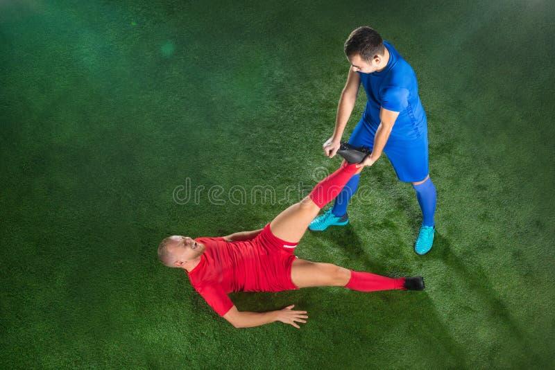 遭受在橄榄球绿色领域的腿伤的男性足球运动员 免版税库存图片