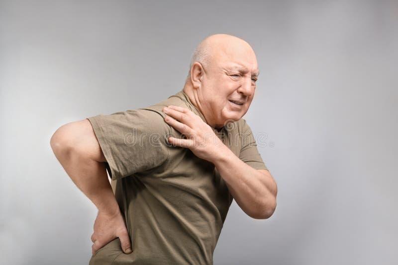 遭受在肩膀的痛苦的老人在轻的背景 库存照片