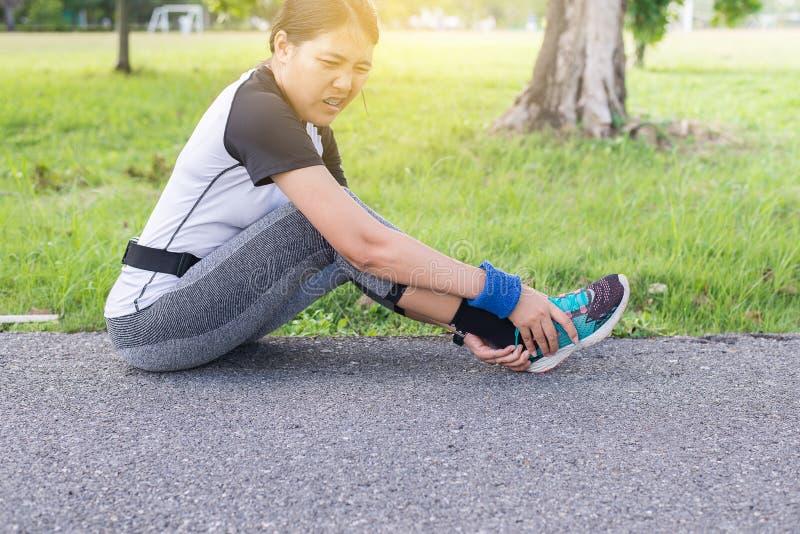 遭受在腿和脚踝受伤的痛苦的妇女在跑跑步以后与锻炼 免版税库存图片