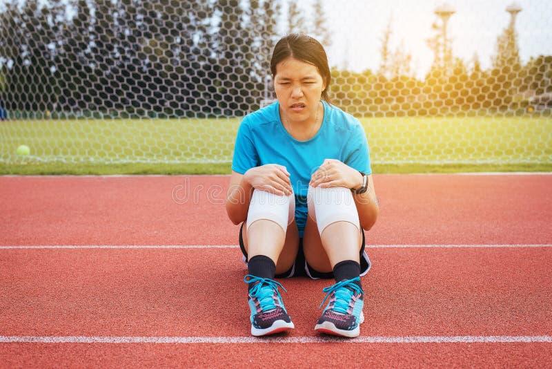 遭受在腿的痛苦的妇女赛跑者被伤害,接触她的膝盖的手在跑步在轨道赛跑以后 库存图片