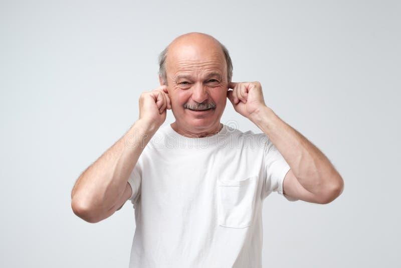 遭受大声音乐和痛苦尖叫的设法的白色T恤杉的成熟人塞住耳朵反对灰色背景 免版税库存图片