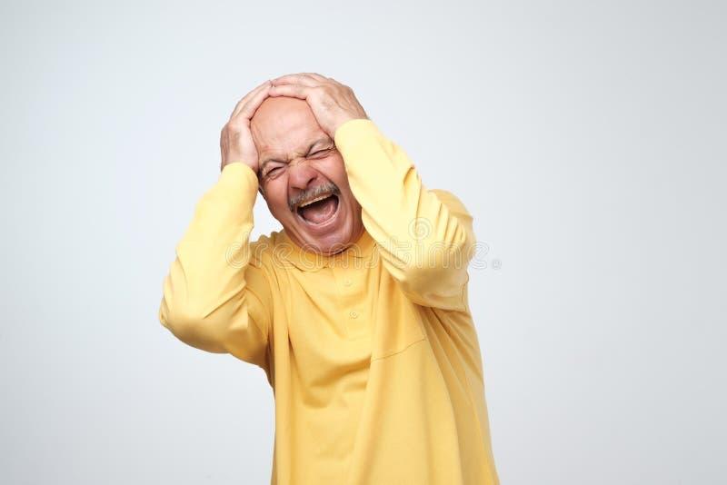 遭受大声音乐和痛苦尖叫的设法的黄色T恤杉的成熟人塞住耳朵反对灰色背景 库存照片