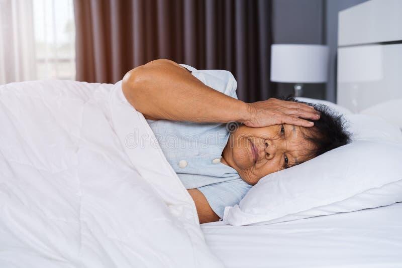 遭受失眠的老妇人在床上设法睡觉 免版税库存照片