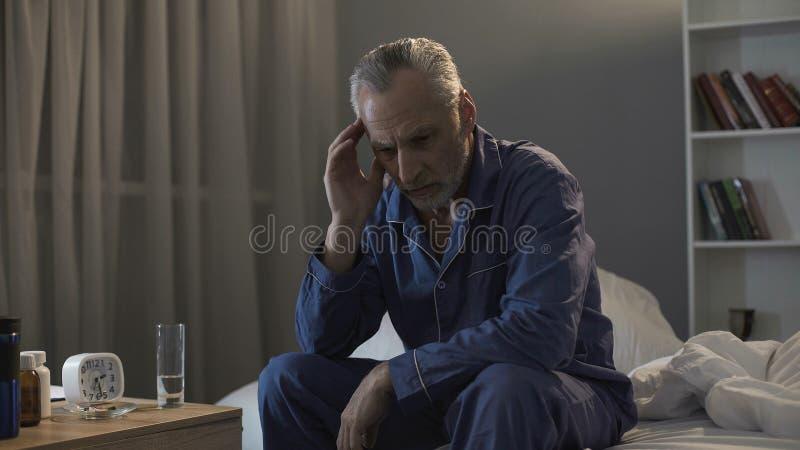 遭受头疼的失眠的老人,坐沙发在夜间 免版税库存图片