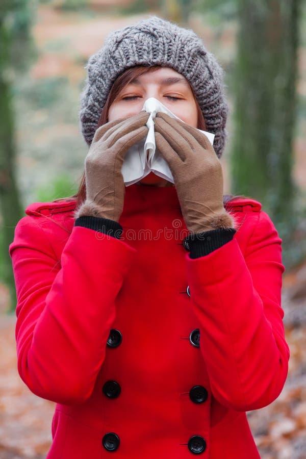 遭受寒冷或流感吹的鼻子或打喷嚏在白皮书手帕的少妇 库存照片