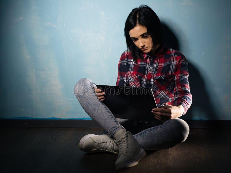 遭受对人脉的依赖性的年轻哀伤的女孩坐与笔记本的地板 免版税图库摄影
