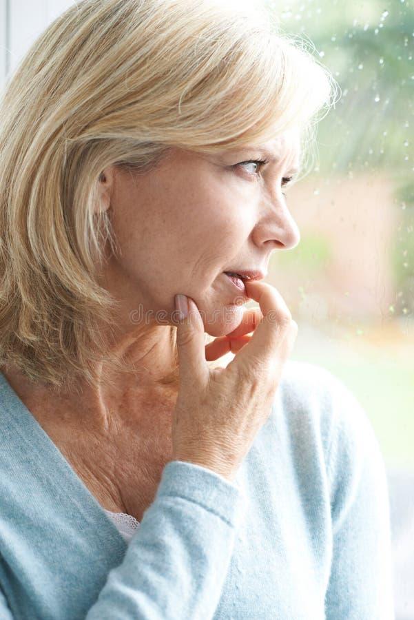 遭受广场恐怖症的哀伤的成熟妇女看在Windo外面 库存图片