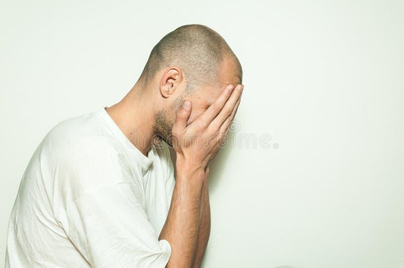 遭受忧虑和感觉的凄惨的盖子他的面孔用他的手和倾斜在白色墙壁上的年轻沮丧的人 免版税库存图片