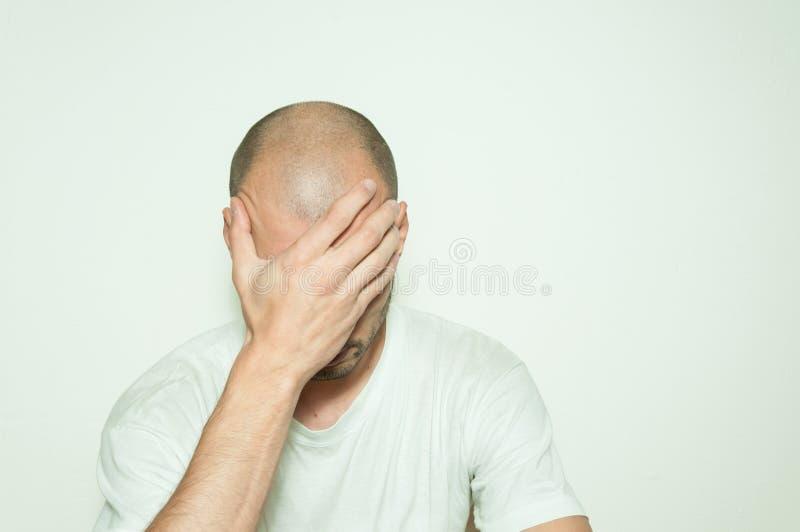 遭受忧虑和感觉的凄惨的盖子他的面孔用他的手和倾斜在白色墙壁上的年轻沮丧的人 库存图片