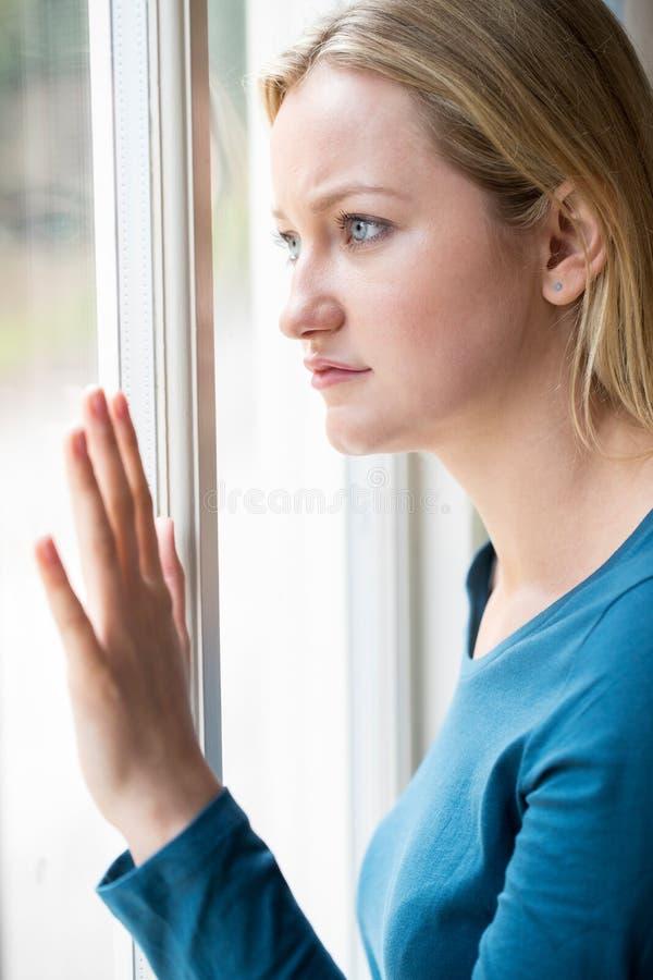 遭受消沉的哀伤的少妇看在窗口外面 库存图片