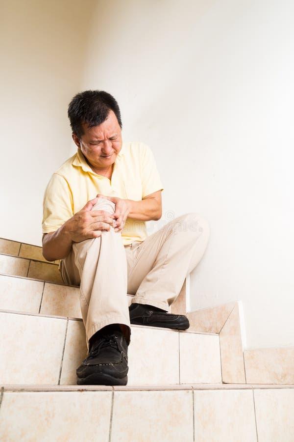 遭受深刻膝盖关节痛苦的成熟的人供以座位在台阶 免版税库存照片