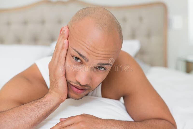 遭受牙痛的秃头人在床上 免版税库存照片