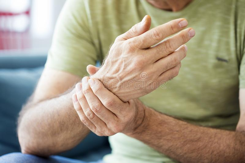 遭受痛苦和风湿病的老人 库存照片