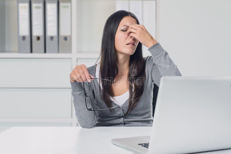 遭受眼睛疲劳的妇女在她的膝上型计算机 图库摄影