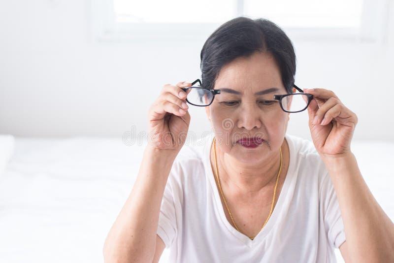 遭受眼睛痛苦手的老年人妇女拿着镜片 库存图片