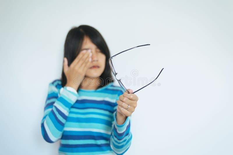 遭受眼睛痛苦的妇女迷离递拿着镜片并且摩擦她的鼻子眼睛在疲乏外面 库存图片