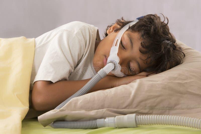遭受睡眠停吸的孩子,戴着呼吸面具 免版税库存照片