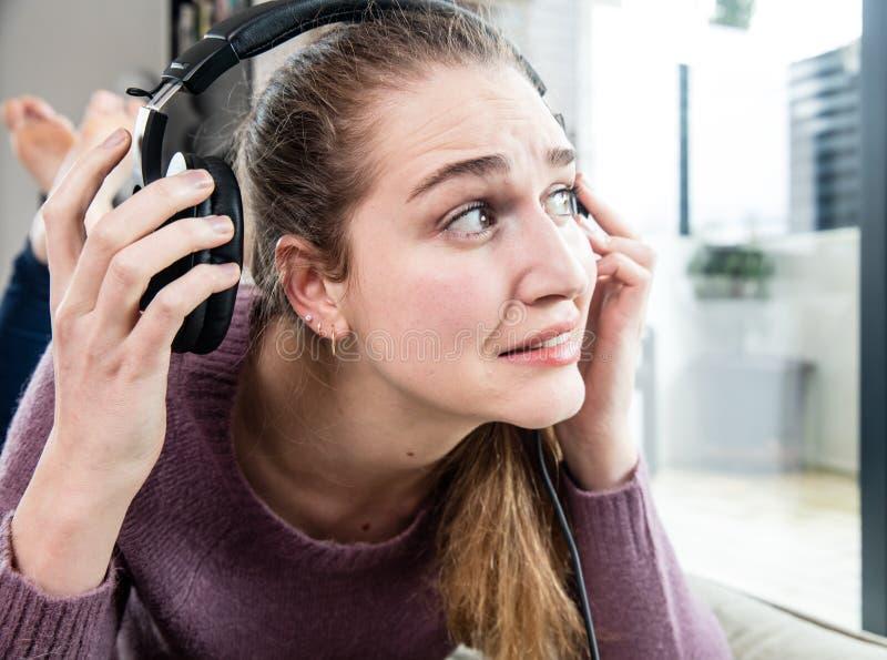 遭受耳鸣或头疼家的惊奇的少妇 库存图片