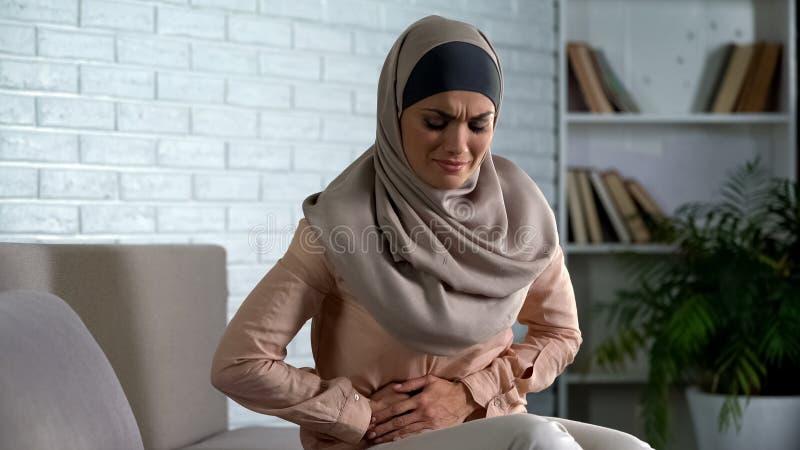 遭受胃肠痛苦,期间抽疯的回教妇女,需要医疗援助 库存照片