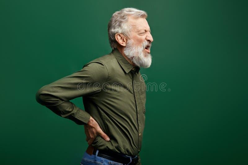 遭受背部疼痛的恼怒的呼喊的老人隔绝在绿色背景 库存照片