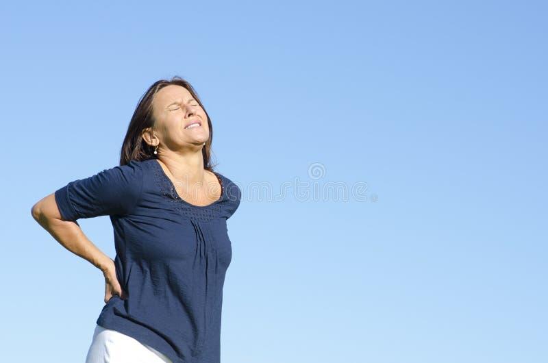 遭受背部疼痛的成熟妇女 图库摄影