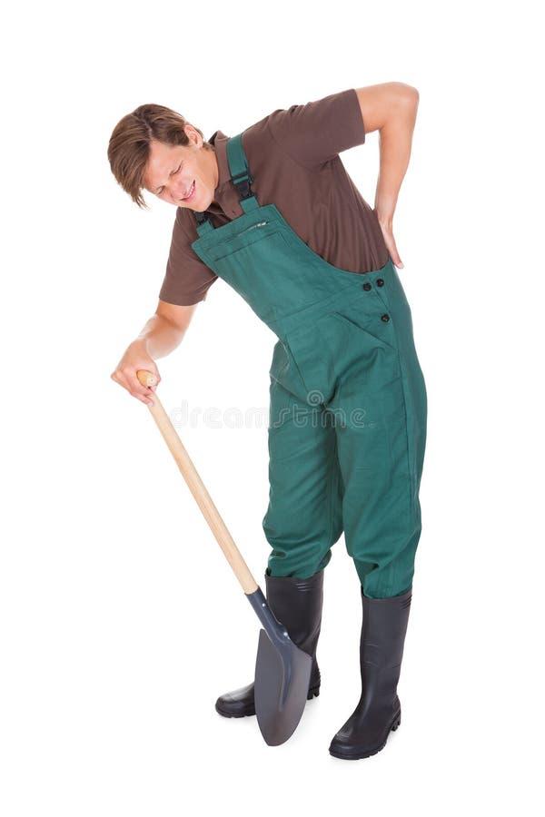 遭受背部疼痛的男性花匠 免版税图库摄影