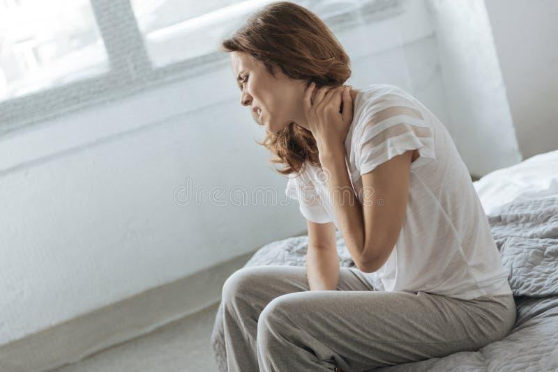 遭受脖子炎症的哀伤的沮丧的妇女 库存照片