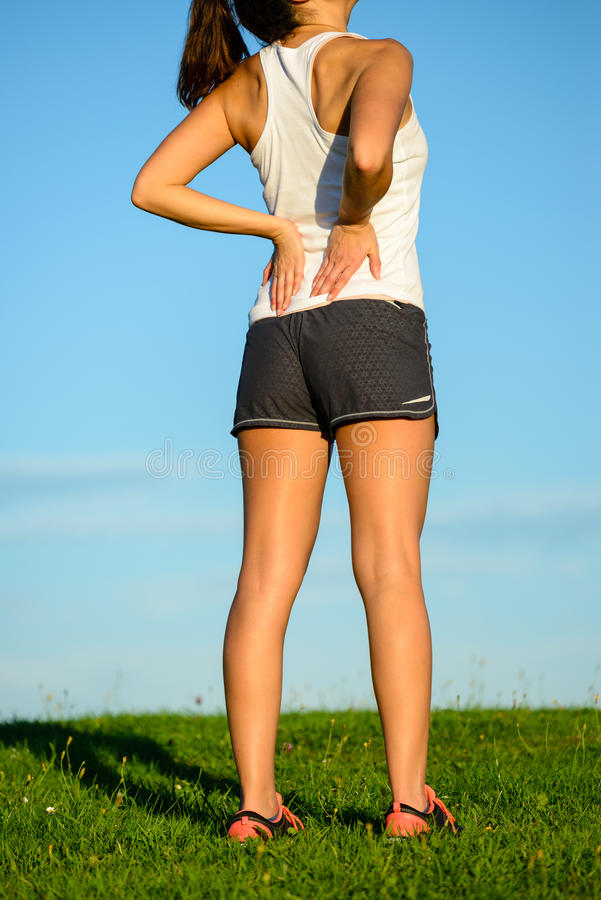 遭受腰下部痛的女运动员 免版税库存图片