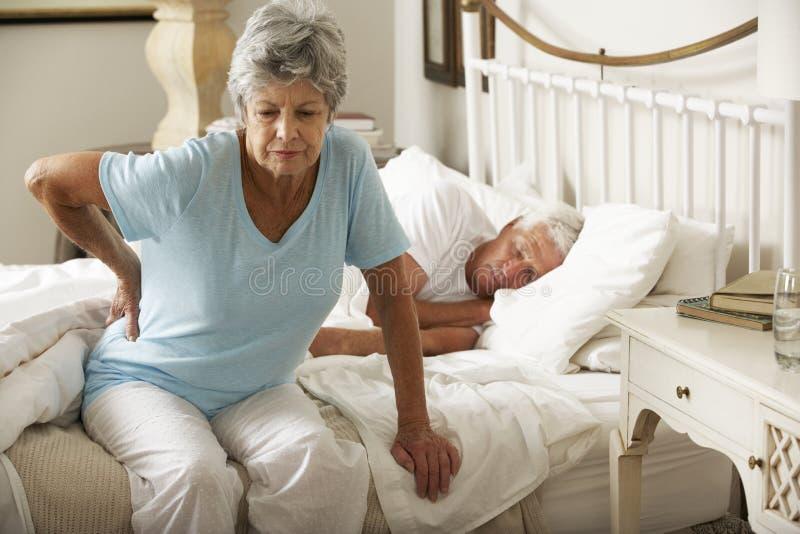 遭受腰疼下的资深妇女床 库存图片