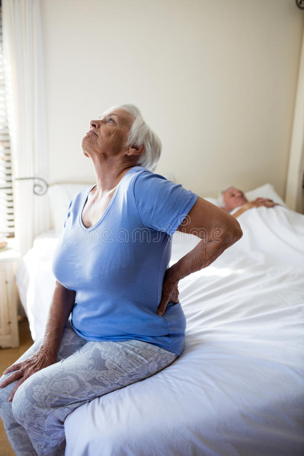 遭受腰疼的资深妇女在卧室 免版税库存图片