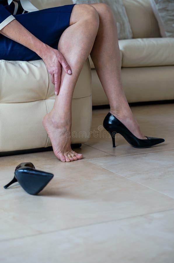 遭受腿痛的资深夫人 黑hig的女商人 免版税库存照片