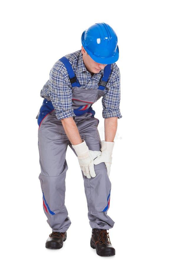 遭受膝盖痛苦的男性工作者 库存图片