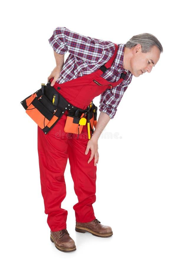 遭受膝盖痛苦的男性技术员 库存图片