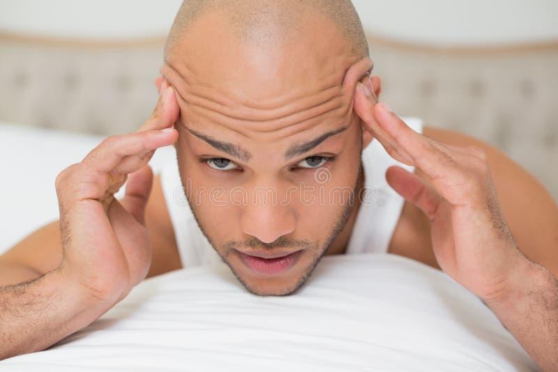 遭受头疼的秃头人在床上 库存照片