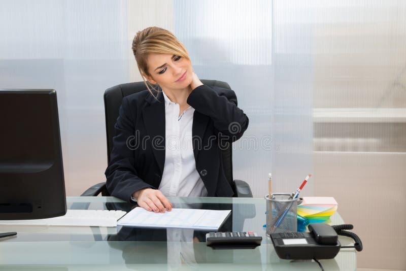遭受neckache的年轻女实业家 免版税库存图片