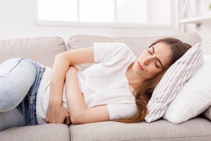 遭受stomachache的女孩躺下在沙发 免版税库存照片