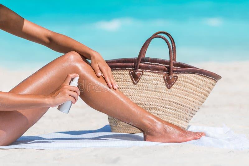 遮光剂把sunblock油放的海滩妇女在腿上 免版税库存照片