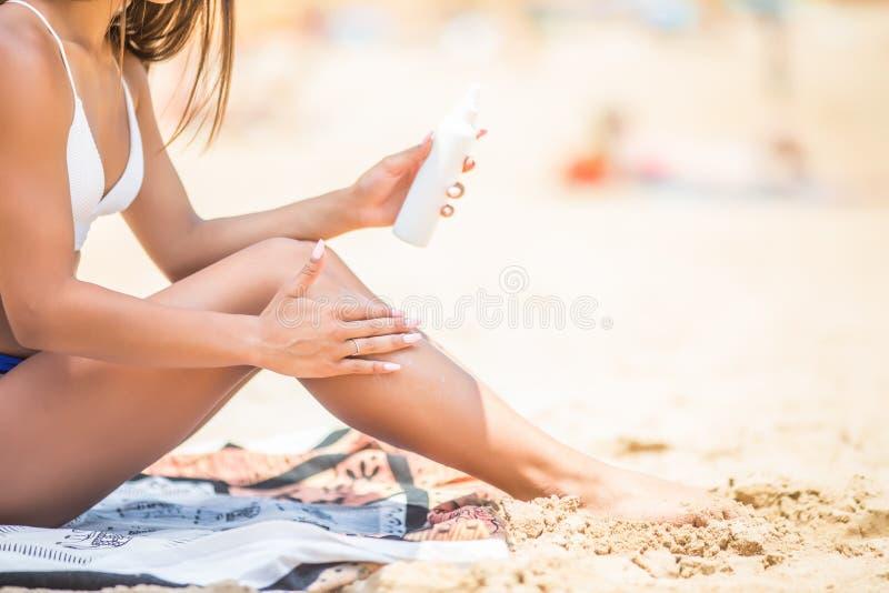遮光剂晒黑化妆水浪花skincare把晒黑的油放的妇女产品特写镜头在她的腿上 举行sunblock瓶spra的手 免版税库存照片